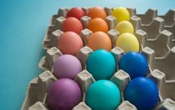 Uova di Pasqua variopinte tinte mano vibrante in una scatola delle uova del cartone osservata Immagine Stock Libera da Diritti