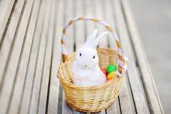 Uova di Pasqua variopinte in un canestro sul banco di legno con il coniglietto bianco sveglio del giocattolo Immagini Stock