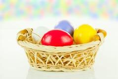Uova di Pasqua Variopinte in un cestino Fotografia Stock