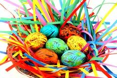 Uova di Pasqua Variopinte in un cestino Immagine Stock
