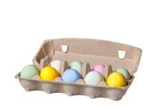Uova di Pasqua variopinte in un vassoio del cartone su fondo di legno Immagine Stock