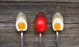 Uova di Pasqua in vecchi cucchiai su fondo di legno immagini stock libere da diritti