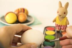 Uova di Pasqua di verniciatura con la spazzola rossa, fotografie stock