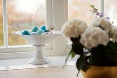 Uova di pietra o di marmo nel supporto bianco accanto ad una finestra Fotografia Stock