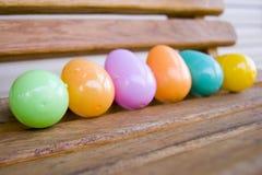 Uova di plastica variopinte su un'oscillazione di legno Fotografia Stock