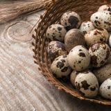 Uova di quaglia in canestro di vimini su fondo di legno fotografia stock