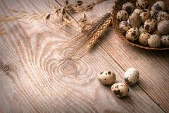 Uova di quaglia in canestro di vimini su fondo di legno fotografie stock