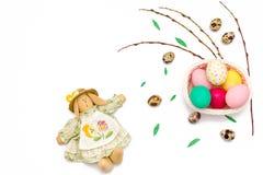 Uova di quaglia, coniglietto di pasqua, rami del salice e merce nel carrello variopinta delle uova su fondo bianco Immagini Stock