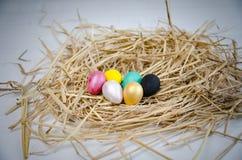 Uova di quaglia dipinte dai mestieri dei bambini per le uova di Pasqua, fatti a mano del manifesto di colore dipinto Immagini Stock