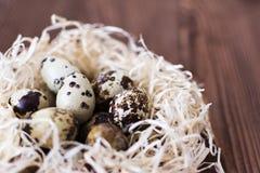 Uova di quaglia in un nido su un fondo di legno Fotografie Stock Libere da Diritti