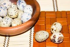 Uova di quaglia in una ciotola di legno su un tovagliolo da bambù naturale Immagini Stock