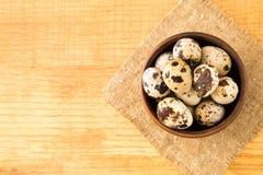 Uova di quaglia in una ciotola sul licenziamento su una superficie di legno, vista superiore, e Immagini Stock Libere da Diritti