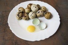 Uova di quaglie su un piatto bianco Un uovo è rotto Immagine Stock