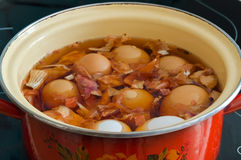 Uova di tintura nella pelle di cipolla Le uova nella pentola sulla stufa Preparazione per Pasqua Fotografie Stock