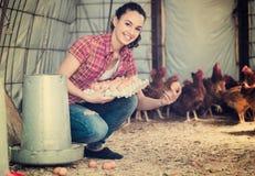 Uova di trasporto dell'agricoltore femminile allegro Fotografie Stock Libere da Diritti