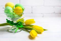 Uova di verde di Pasqua, tulipani gialli, spazio della copia immagine stock