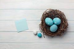 Uova dipinte blu in nido ed in salice purulento Cartolina d'auguri di Pasqua Vista superiore con spazio per i vostri saluti immagini stock libere da diritti