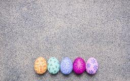 Uova dipinte luminose e variopinte per Pasqua, presentate in un posto del confine di fila per la fine rustica di vista superiore  fotografia stock libera da diritti
