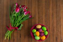 Uova dipinte variopinte di Pasqua e mazzo di tulipani Fotografie Stock Libere da Diritti