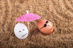 Uova divertenti di Pasqua sotto l'ombrello su una sabbia Fotografia Stock