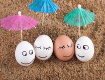 Uova divertenti di Pasqua sotto l'ombrello su una sabbia Fotografia Stock Libera da Diritti