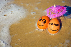 Uova divertenti di Pasqua sotto l'ombrello su una spiaggia Immagini Stock
