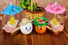 Uova divertenti nel cappello e nella corona Con i panini e gli ombrelli Fotografie Stock Libere da Diritti