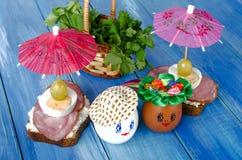 Uova divertenti nel cappello e nella corona Con i panini e gli ombrelli Immagine Stock