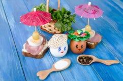 Uova divertenti nel cappello e nella corona Con i panini e gli ombrelli Fotografie Stock