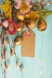 Uova dorate della quaglia, alstroemeria del salice su un'etichetta di legno blu del fondo Fotografia Stock Libera da Diritti
