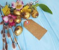 Uova dorate della quaglia, fiore di alstroemeria del salice su un'etichetta di legno blu del fondo Fotografia Stock