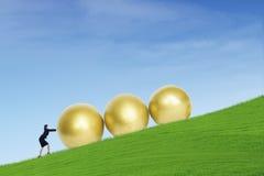 Uova dorate di spinta della donna di affari sulla collina Immagini Stock Libere da Diritti