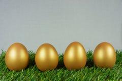 Uova dorate su un verde Fotografie Stock