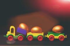 Uova dorate tradizionali in giocattolo o locomotiva variopinto di plastica dell'automobile Fotografie Stock Libere da Diritti