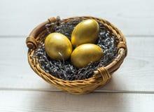 Uova dorate in un cestino Immagine Stock