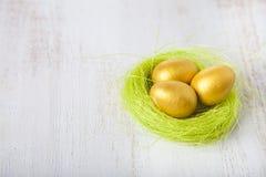 Uova dorate in un nido su un fondo di legno Immagine Stock
