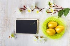Uova dorate in un nido su un fondo di legno Fotografie Stock