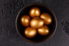 Uova dorate in una tazza nera su un fondo strutturato nero Uova di Pasqua Wiev superiore Immagini Stock