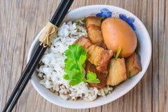 Uova e carne di maiale in salsa marrone, cucina tailandese, uova sode con il 'chi' Immagini Stock
