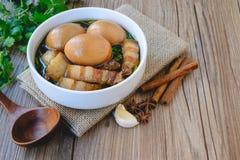 Uova e carne di maiale in salsa marrone, cucina tailandese, uova sode con il 'chi' Fotografia Stock