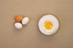 Uova e primo piano della farina sulla tavola Fotografie Stock Libere da Diritti