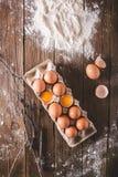 Uova ed uova rotte nel pacchetto su un fondo di legno Era la farina sparsa su una tavola di legno fotografia stock