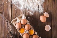 Uova ed uova rotte nel pacchetto su un fondo di legno Era la farina sparsa su una tavola di legno eggshell cottura immagine stock libera da diritti