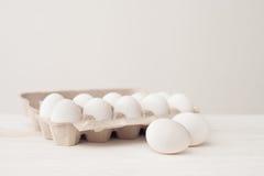 Uova, fondo bianco, tavola, imballante per le uova fatte del cardbo Fotografia Stock Libera da Diritti