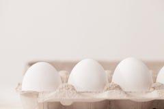 Uova, fondo bianco, tavola, imballante per le uova fatte del cardbo Fotografia Stock