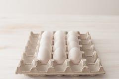 Uova, fondo bianco, tavola, imballante per le uova fatte del cardbo Immagini Stock