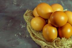 Uova fresche dell'azienda agricola di marrone del pollo su tela da imballaggio e su fondo grigio fotografia stock libera da diritti