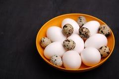 Uova fresche di quaglia e del pollo sul piatto giallo Vista superiore Alimento sano e concetto di agricoltura biologica Immagini Stock