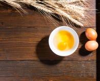 Uova fresche in una ciotola con le orecchie di grano Fotografia Stock Libera da Diritti