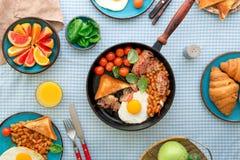 Uova fritte, bacon, pomodori, fagioli e spinaci in pentola Immagini Stock